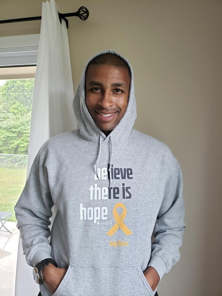 A man wearing a grey 2020 ACCO Cancer Awareness Month hoodie.